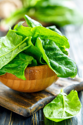 Wooden bowl with fresh spinach leaves in water drops.